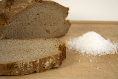 Sliced bread and salt. Loaf of bread and a slice of bread next to some salt Royalty Free Stock Photography