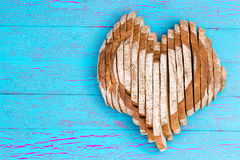 Sliced bread shaped as heart on old blue table Stock Photography