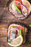 Sliced bread with smoked salmon, herring, lemon and arugula closeup Royalty Free Stock Photography