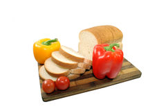 Sliced bread with vegetables. A couple of sliced bread with vegetables on a wooden plate Stock Photos