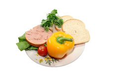 Sliced bread with vegetables. A couple of sliced bread with vegetables on a white plate Royalty Free Stock Image