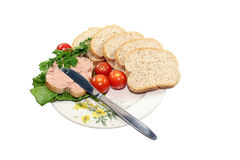 Sliced bread with vegetables. A couple of sliced bread with vegetables and a silver knife on a white plate Royalty Free Stock Photography