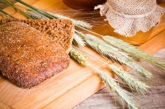 Sliced bread and wheat Stock Images