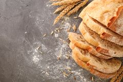 Sliced bread with wheat spikes and flour. On grey table closeup Royalty Free Stock Images