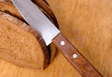Sliced bread on a wooden cutting board and knife Royalty Free Stock Images