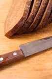 Sliced bread on a wooden cutting board and knife Royalty Free Stock Photography