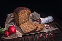 Sliced brown bread, salami, radish and dry pepper on paper over Royalty Free Stock Images