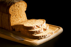 Sliced brown bread on wooden chopping board Stock Images