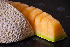 Sliced cantaloupe on black bench. Sliced cantaloupe and a section showing intricate peel pattern on black bench Stock Image