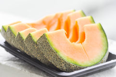 Sliced cantaloupe dish. In blur background royalty free stock image