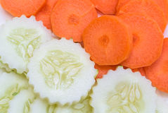 Sliced carrot and cucumber. Group of round shape sliced carrot and cucumber on white plate Stock Photography