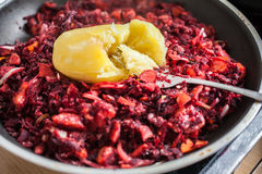 Sliced carrot, red beet and onion with cooked potato on top. Sliced carrot, red beet and onion mixed with potato on top in a frying pan stock photo