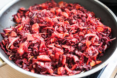 Sliced carrot, red beet and onion mixed with flour. In a frying pan stock image