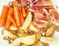 Sliced carrots, apple, grapefruit, oranges and walnuts, fruit th Royalty Free Stock Photos