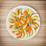 Sliced carrots, apple, kiwi, tangerine, and oranges on the white Royalty Free Stock Image