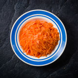 Sliced carrots in a bowl on black stone background. Royalty Free Stock Photo