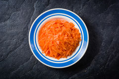 Sliced carrots in a bowl on black stone background. Stock Photography