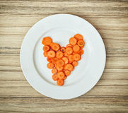 Sliced carrots in the heart shape on the white plate, Valentine' Royalty Free Stock Photos