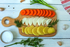 Sliced carrots, onions and potatoes on a cutting board. Cooking soup. Flat view Stock Photo