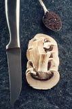 Sliced champignon mushrooms. On stone background stock photography