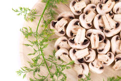 Sliced champignons on cutting board. Royalty Free Stock Images
