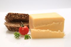 Sliced cheese with a cherry tomato on the side. And some bread Stock Image