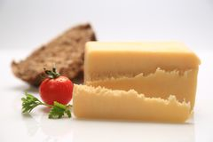 Sliced cheese with a cherry tomato on the side. And some bread Royalty Free Stock Images