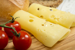 Sliced cheese and cherry tomatoes on wooden chopping board Royalty Free Stock Image