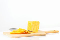 Sliced cheese with a knife on a cutting board Stock Photo