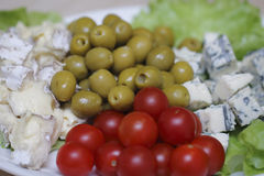 Sliced cheese, olives and tomatoes Stock Images
