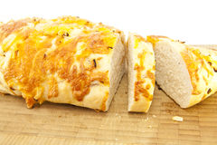 Sliced Cheese and Onion Loaf. Sliced Cheese and Onion Bread on a wooden cutting board isolated on a white background Stock Photos
