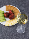 Sliced cheese on a plate with a glass of wine. Stock Photo