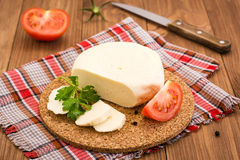 Sliced cheese, tomato and parsley leaves on a substrate on a wooden table Royalty Free Stock Photo
