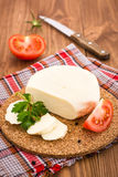 Sliced cheese, tomato and parsley on a substrate on a wooden table Stock Photo