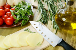 Sliced cheese, tomatoes and herbs on a kitchen table top view cl Stock Images