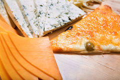 Sliced cheeses and pizza Royalty Free Stock Photos