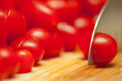 Sliced cherry tomatoes. A Sliced Cherry Red Tomato on a cutting board stock photo