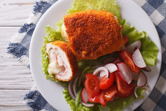 Sliced Chicken cordon bleu and salad close-up. Horizontal top vi Stock Image