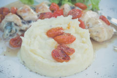 Sliced chicken with mashed potato and tomato cherry in italian sauce. Italian restaurant. Bali island. delicious dinner. Royalty Free Stock Images