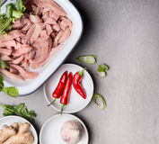 Sliced chicken or turkey meat with spices and fresh seasoning for clean diet cooking on gray concrete background, top view. Place for text royalty free stock photography