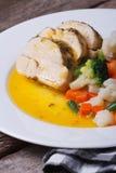 Sliced chicken with vegetables in orange sauce vertical Stock Photo