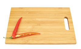 Sliced chili pepper over a cutting board. Isolated over white background Royalty Free Stock Photography