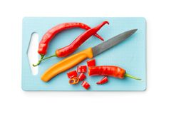 Sliced chili peppers and knife on cutting board. Sliced chili peppers and knife on cutting board isolated on white background. Top view Stock Photo