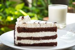 Sliced chocolate cake on white plate. Served on wooden table wit Royalty Free Stock Photos