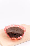 Sliced chocolate muffin on the wooden board in paper wrapper.  Royalty Free Stock Photo