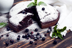 Sliced chocolate pie with mint and ingredients on table. Chocolate pie on wooden table. Vegan cake stock images