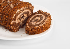 Sliced chocolate roll on white dish Stock Photos