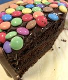 A sliced chocolate sponge cake with topping of sweets Royalty Free Stock Photography