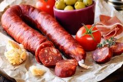 Sliced chorizo. Sliced Spanish chorizo sausage with bread, olives, jamon serrano and tomatoes stock photography