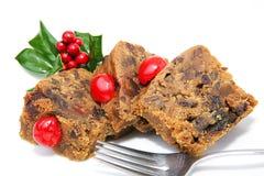 Sliced Christmas Fruitcake. Slices of Christmas fruitcake isolated on white with holly garnish and fork Stock Images